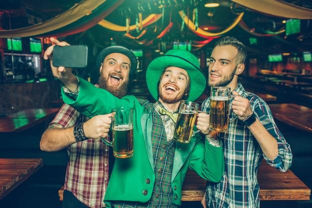 Hombres jovenes felices que toman selfie juntos en pub. el chico del medio usa el traje de san patricio y sostiene el teléfono en las manos. ellos sonrien.