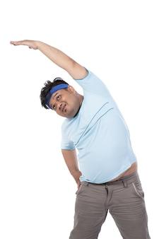 Hombres jóvenes gordos calientan los músculos abdominales