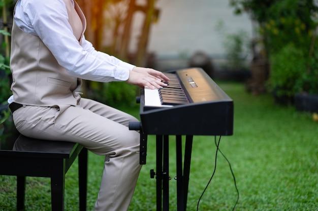 Hombres jovenes hermosos que tocan el piano electrónico negro de lujo en el jardín