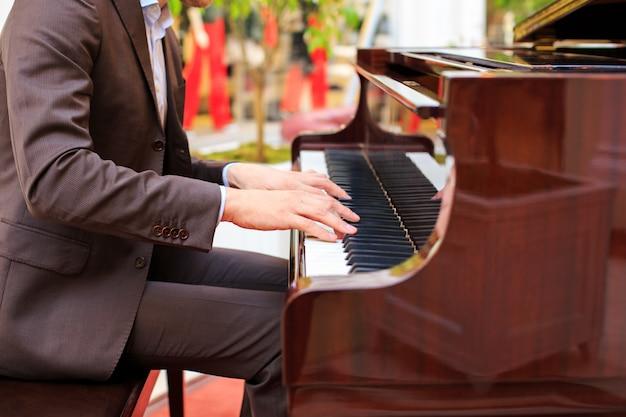 Hombres jovenes hermosos que tocan el piano