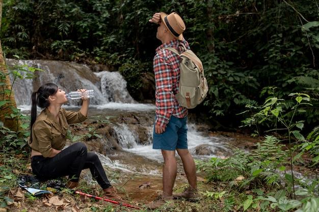 Hombres jóvenes y jóvenes y excursionistas beben agua dulce.
