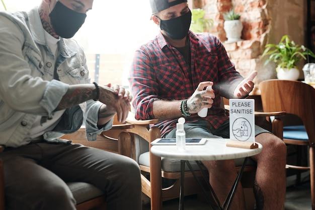 Hombres jóvenes con máscaras negras sentados en sillas en un café moderno y rociar las manos con desinfectante