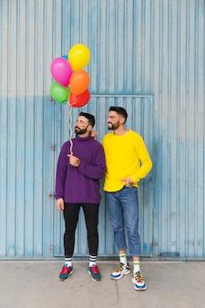 Hombres jóvenes de pie con globos