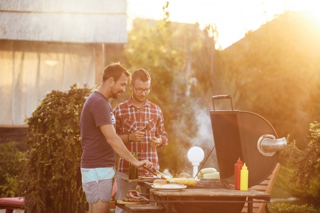 Hombres jovenes que asan la barbacoa en parrilla en campo de la cabaña.