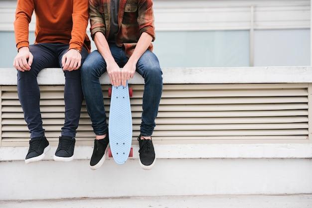 Hombres jovenes que se sientan en la cerca con longboard