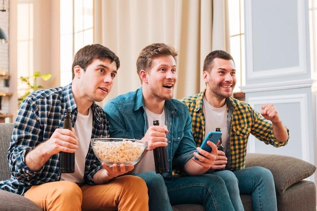 Hombres jovenes que se sientan en el sofá que mira acontecimiento deportivo en la televisión en casa