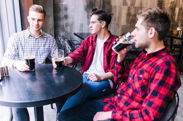 Hombres jóvenes sentados juntos bebiendo la cerveza con su amigo