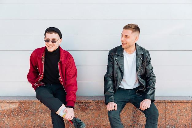 Hombres jóvenes sentados en parapeto y sonriendo
