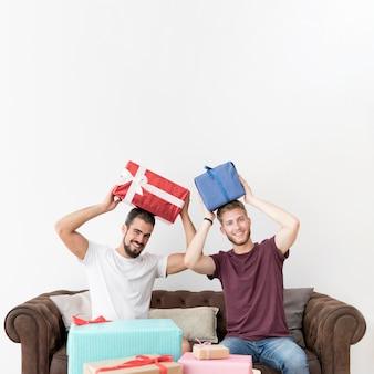 Hombres jovenes sonrientes que se sientan en el sofá que sostiene las cajas de regalo en su cabeza