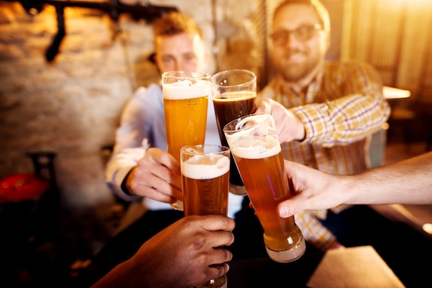 Hombres jóvenes tintineando vasos con una cerveza en el pub soleado.