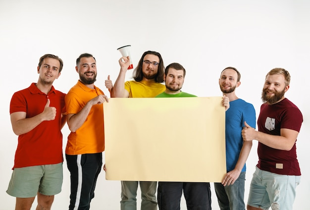 Los hombres jóvenes vestían los colores de la bandera lgbt aislados en la pared blanca. modelos masculinos caucásicos en camisetas de color rojo, naranja, amarillo, verde, azul y morado. orgullo lgbt, derechos humanos, concepto de elección. copyspace.