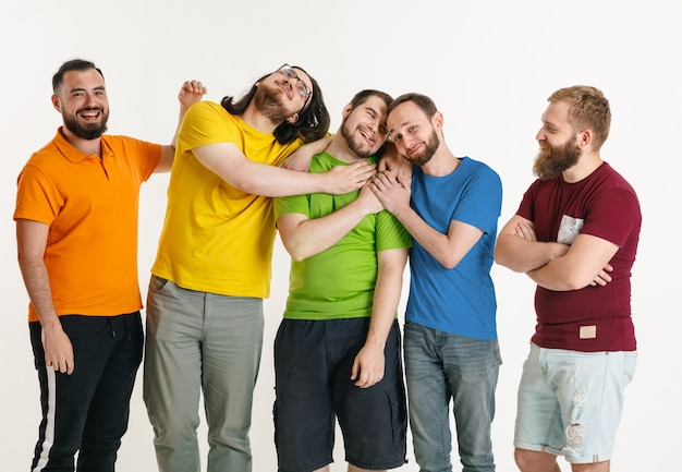 Los hombres jóvenes vestían los colores de la bandera lgbt aislados en la pared blanca. modelos masculinos caucásicos en camisetas de color rojo, naranja, amarillo, verde, azul y morado. orgullo lgbt, derechos humanos y concepto de elección.
