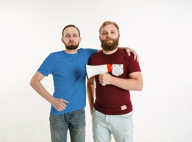 Los hombres jóvenes vestían los colores de la bandera lgbt en la pared blanca.
