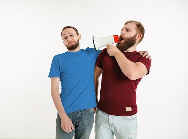 Hombres jóvenes vistiendo camisetas de colores y sosteniendo el megáfono en la pared blanca