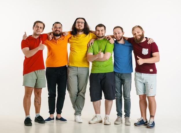 Los hombres jóvenes se vistieron con los colores de la bandera lgbt aislados en la pared blanca