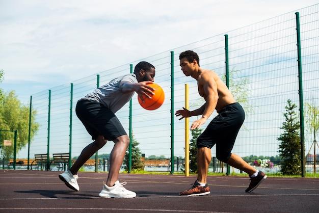 Hombres jugando baloncesto urbano bajo ángulo de tiro