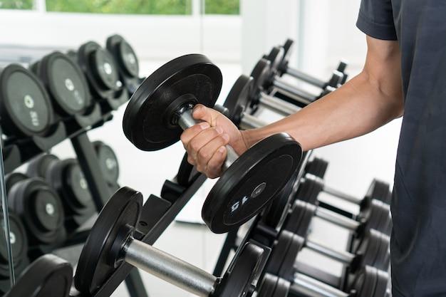 Hombres levantando pesas con mancuernas preparándose para hacer ejercicio en fitness.