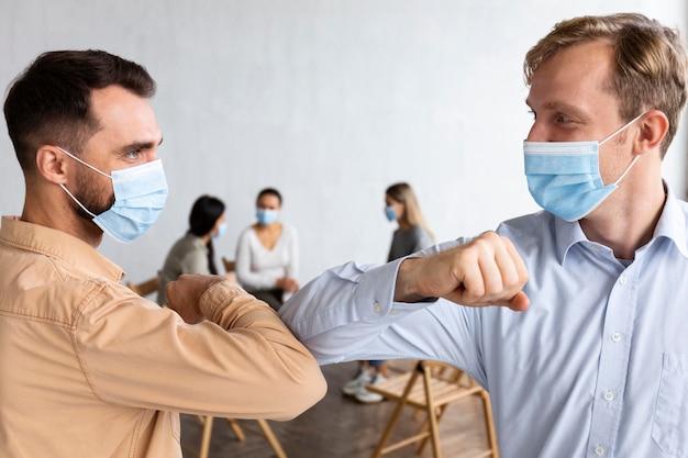 Hombres con máscaras médicas en una sesión de terapia de grupo haciendo el saludo del codo