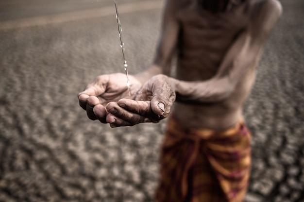 Los hombres mayores están expuestos al agua de lluvia en clima seco, el calentamiento global