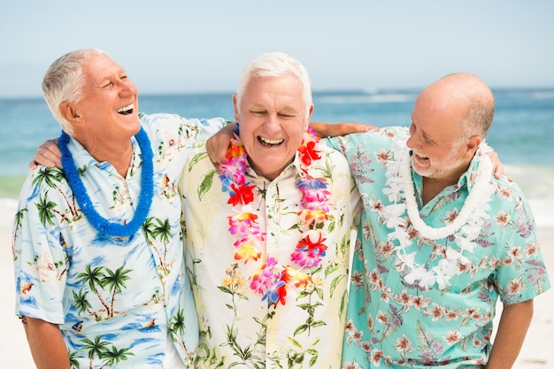 Hombres mayores de pie en la playa