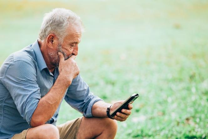Hombres mayores que usan un smartphone mientras está sentado en la hierba en el parque