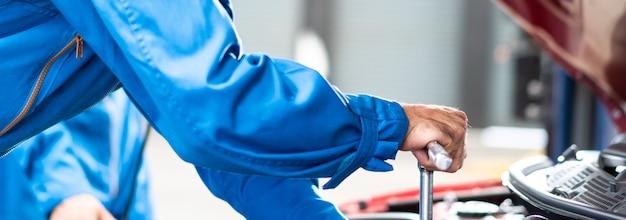 Hombres mecánicos reparación de daños en el coche en el taller de reparación de automóviles