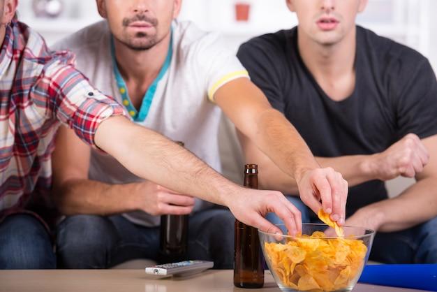 Los hombres miran fútbol en casa con cerveza y papas fritas.