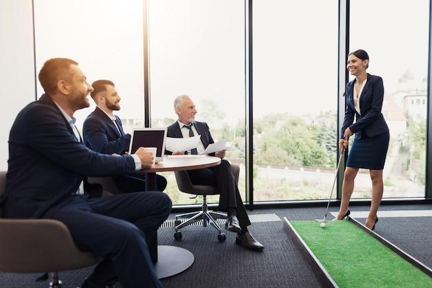 Hombres miran a la mujer en un traje de negocios jugando mini golf