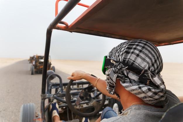 Hombres montando coche buggy en el desierto