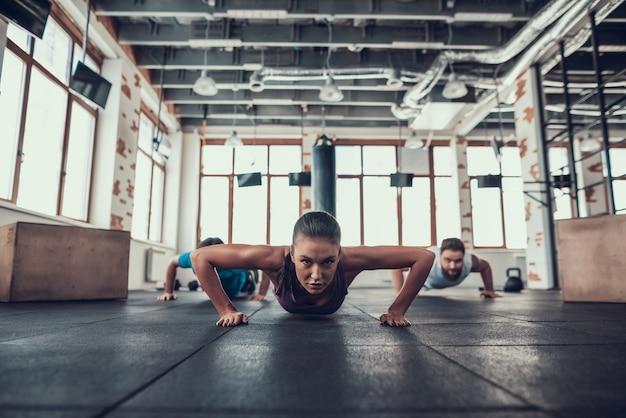 Hombres y mujer haciendo push ups en el gimnasio brillante.