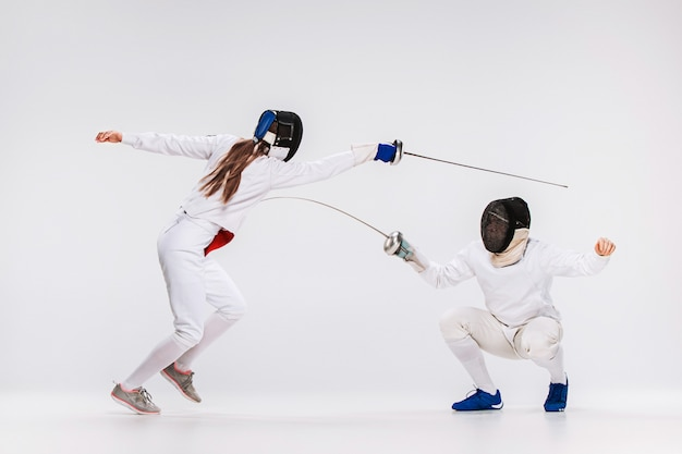 Los hombres y la mujer con traje de esgrima practicando con espada contra gris