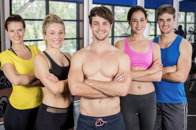 Hombres y mujeres atléticos que presentan los brazos cruzados en el gimnasio del crossfit