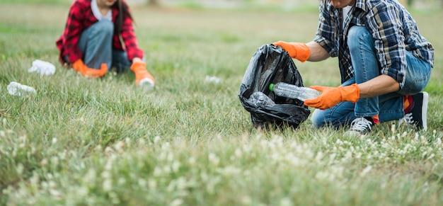 Hombres y mujeres se ayudan mutuamente para recolectar basura.
