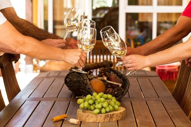 Hombres y mujeres brindando con copas de vino tinto en una mesa de madera