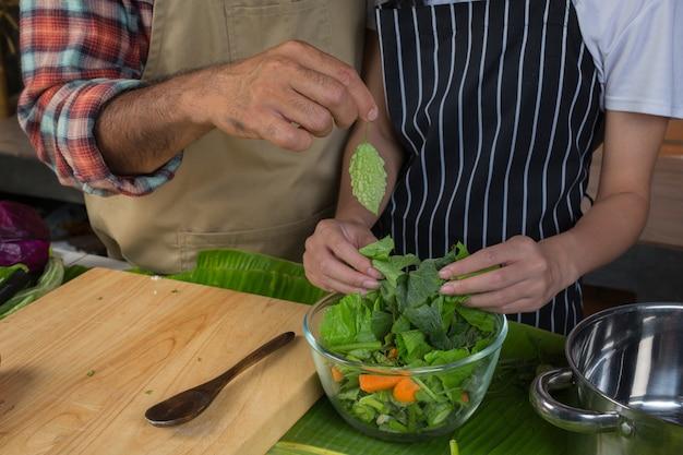 Hombres y mujeres están ayudando a separar las verduras en una taza transparente en la cocina con una pared de ladrillo rojo.