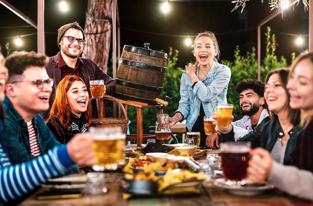 Hombres y mujeres felices divirtiéndose bebiendo en el jardín de la cerveza