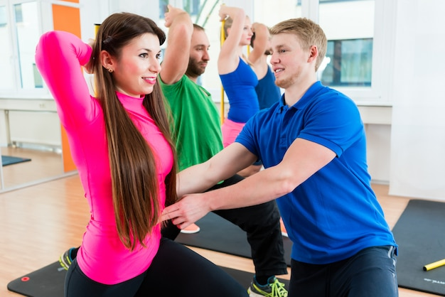 Hombres y mujeres en el gimnasio haciendo ejercicios de pilates
