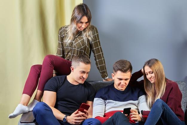 Hombres y mujeres jóvenes en una cita romántica doble miran las pantallas de los teléfonos móviles.