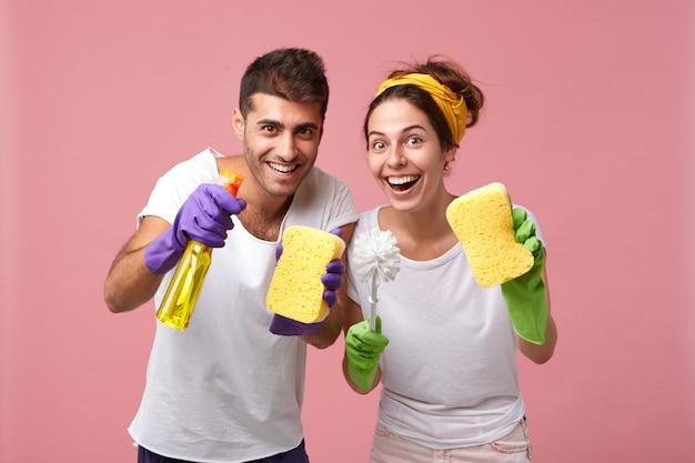 Hombres y mujeres jóvenes felices emocionados con guantes de goma, sosteniendo artículos de limpieza mientras arreglan en su apartamento