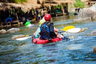 Los hombres y mujeres jóvenes hacen rafting en el río.