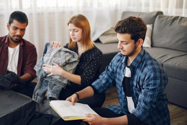 Hombres y mujeres jóvenes que se preparan para un viaje. viajeros empacando ropa y equipaje en una maleta.