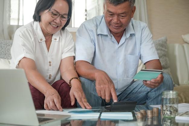 Los hombres y mujeres de jubilación controlan sus ahorros con una expresión feliz.