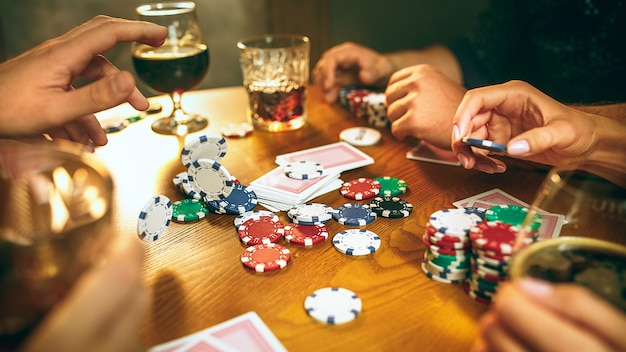 Hombres y mujeres jugando al juego de cartas. poker, entretenimiento nocturno y concepto de emoción.