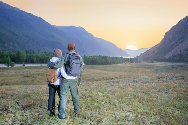 Hombres y mujeres con mochilas disfrutando del atardecer durante la caminata en la montaña