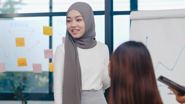 Hombres y mujeres de negocios asiáticos reunidos para intercambiar ideas