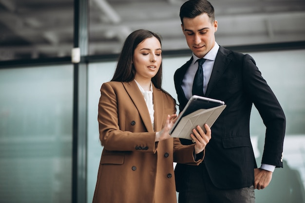 Hombres y mujeres de negocios trabajando en tableta en la oficina