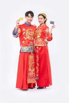 Hombres y mujeres que usan qipao van de compras con tarjetas de crédito.