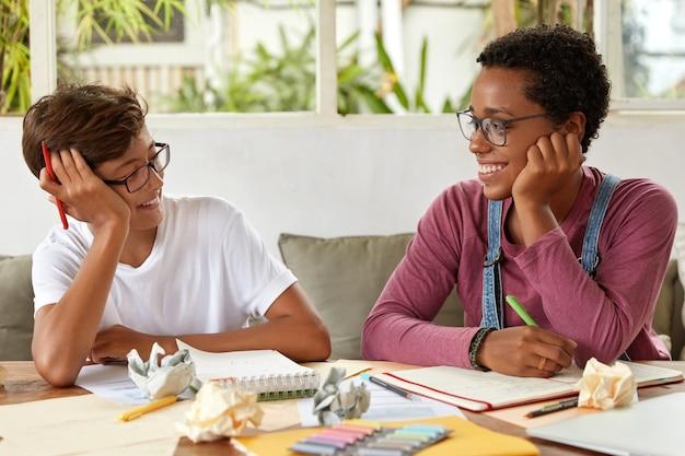 Hombres y mujeres de raza mixta positivos se miran con alegría, trabajan en la investigación
