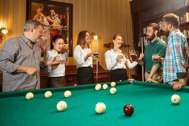 Hombres y mujeres sonrientes jovenes que juegan al billar en la oficina o en casa después del trabajo. compañeros de trabajo involucrados en actividades recreativas. amistad, actividad de ocio, concepto de juego.