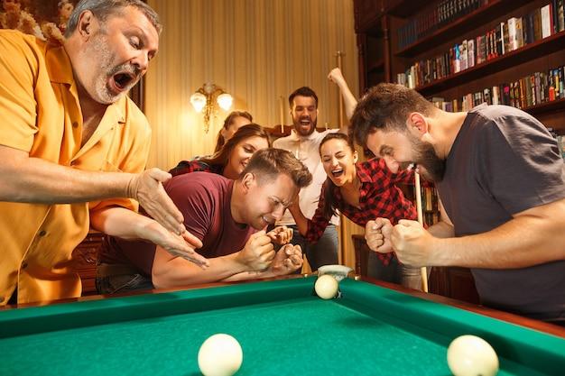 Hombres y mujeres sonrientes jovenes que juegan al billar en la oficina o en casa después del trabajo. compañeros de trabajo involucrados en actividades recreativas.